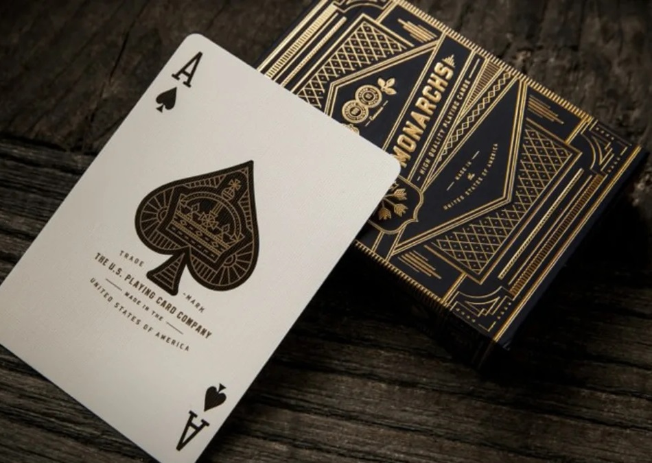 A decorative Ace of Spades in front of a pack of Gold Monarch playing cards.