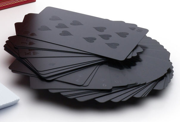 A messily stacked pile of matte black playing cards.